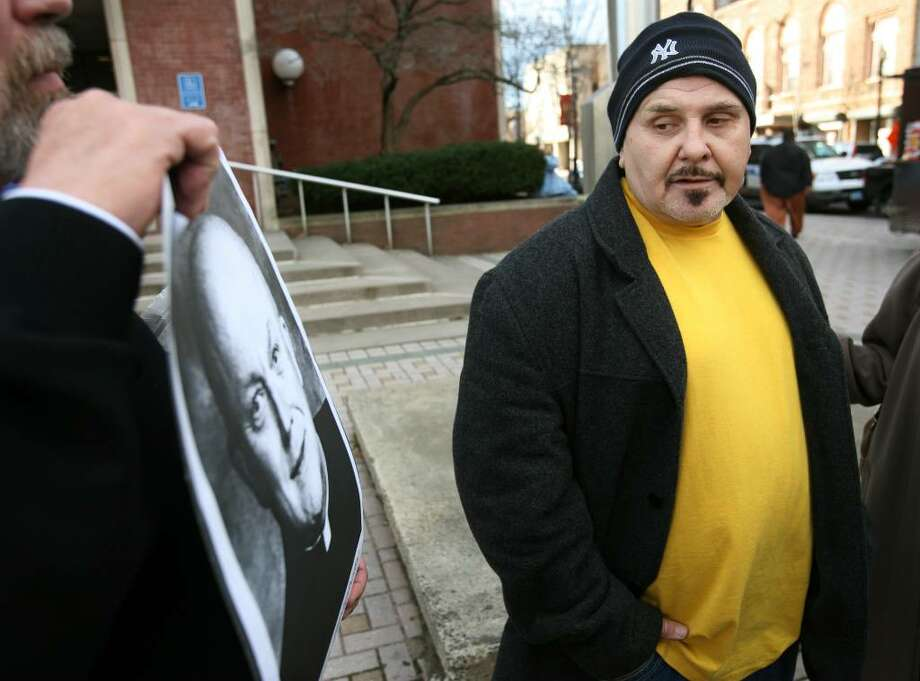 Stephen Kali, 59 of Stamford, eyes the photograph of the priest, Alfred Bietighofer, that he claims sexually abused him as a boy in the early 1960's on Bridgeport's West Side. Kali was walking past a protest outside Bridgeport Superior Court at 1061 Main Street when he noticed a protestor holding Bietighofer's picture. Kali, who said he was 13 or 14 and a freshman at Bassick High School at the time of the abuse, said that this was the first time he had spoken publicly about it. Photo: Brian A. Pounds / Connecticut Post