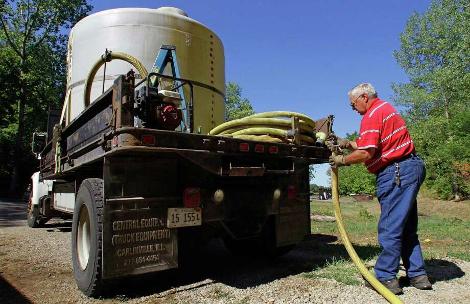 In this Aug. 5, 2012 photo, water hauler Carl Marion of Athens, Ill., pumps water from his 2,000 gallon water tank on the back of his truck into a campground well in Petersburg, Ill. Across the Midwest the drought is leaving many rural homes and businesses that rely on water wells dry. (AP Photo/Seth Perlman) Photo: Seth Perlman / AP