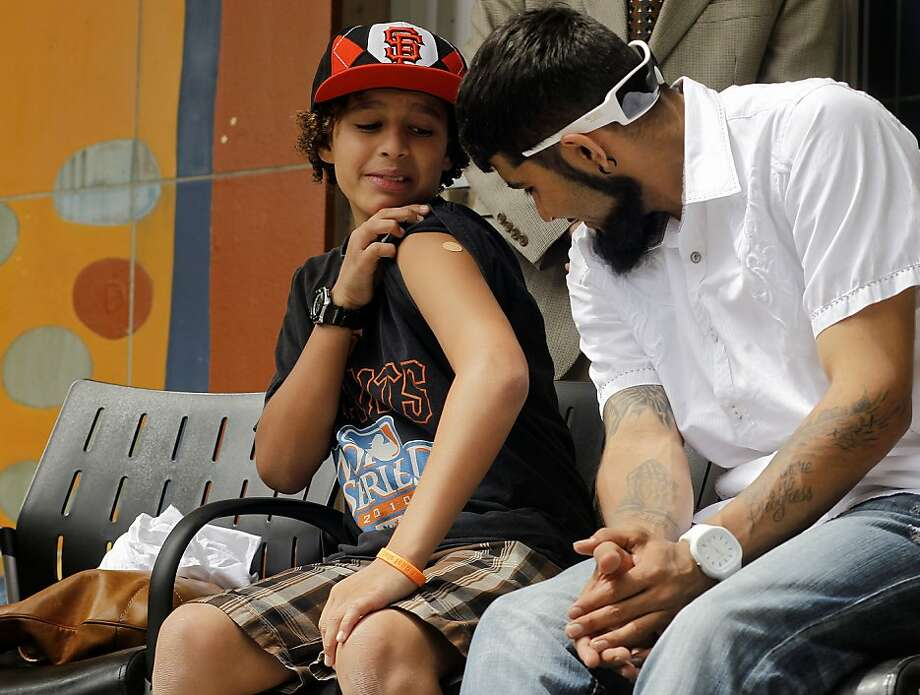 The chance to meet San Francisco Giants reliever Sergio Romo (right) was enough to excite Laith Cuyjet about his Tdap booster vaccine shot. Photo: Michael Macor, The Chronicle