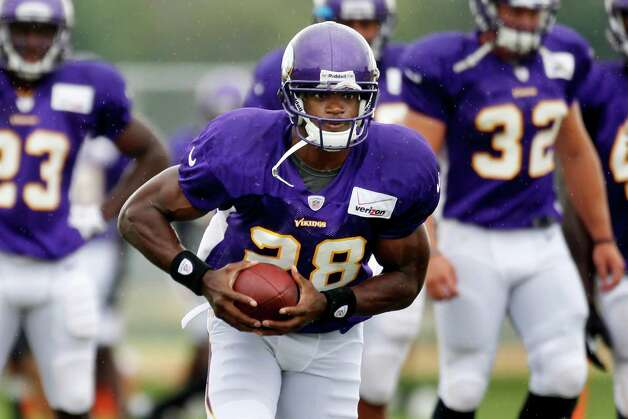 Minnesota Vikings running back Adrian Peterson rushes with the ball during training camp, Tuesday, Aug. 14, 2012, in Mankato, Minn. (AP Photo/The Star Tribune, Jerry Holt) Photo: Jerry Holt, Associated Press / The Star Tribune