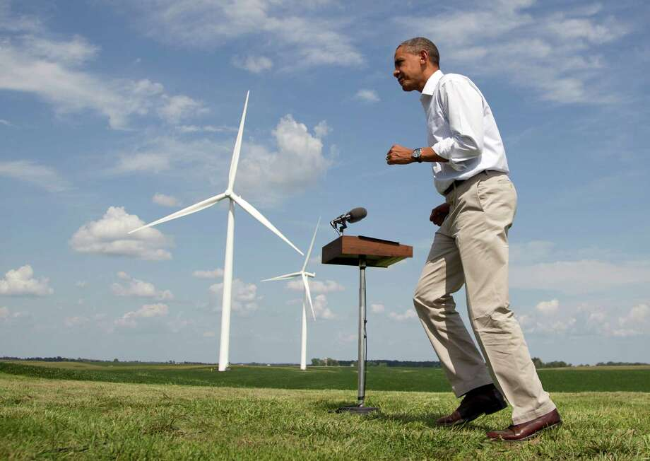 As wind turbines turn on the distance, President Barack Obama changes direction as he walks from a podium after speaking at the Heil family farm , Tuesday, Aug. 14, 2012, in Haverhill, Iowa, during a three day campaign bus tour through Iowa.  (AP Photo/Carolyn Kaster) Photo: Carolyn Kaster / AP