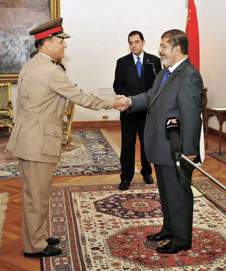 In this photo released by Middle East News Agency, former Armed Forces Chief of Staff Sami Anan, left, shakes hands with Egyptian President Mohammed Morsi at the Presidential Palace in Cairo, Egypt, Tuesday, Aug. 14, 2012. Egypt's president has given awards to the nation's two top military commanders, two days after he ordered their retirement. Tantawi, who ruled Egypt through his military council for 17 months after last year's popular uprising overthrew longtime President Hosni Mubarak, and his chief of staff, Anan, made their first public appearance to receive the nation's highest medal. (AP Photo/Middle East News Agency, HO) Photo: Uncredited / Middle East News Agency