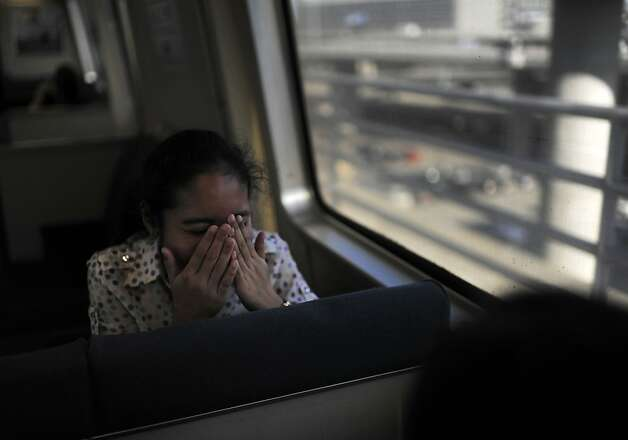 Putri Siti Dyannie covers her face while laughing with her friends on BART on their way to the airport for their summer vacation to New York on Friday, July 27, 2012 in San Francisco, Calif. Photo: Yue Wu, The Chronicle