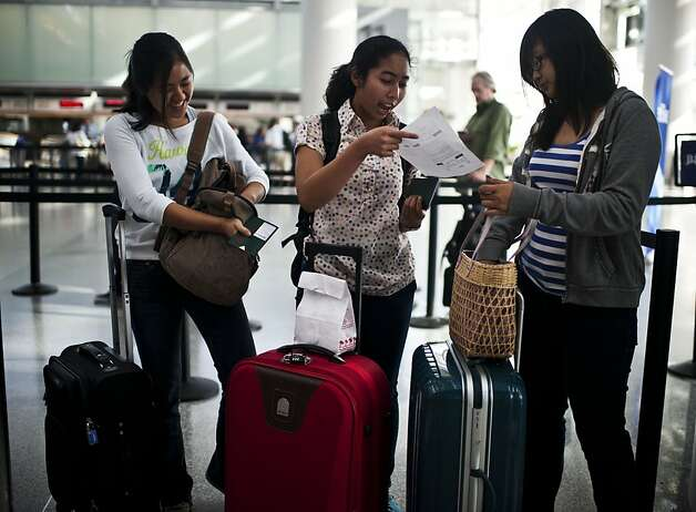 Putri Siti Dyannie, center, takes out her plane ticket to New York and passport before she checks in at San Francisco International Airport on Friday, July 27, 2012 in San Francisco, Calif. Photo: Yue Wu, The Chronicle