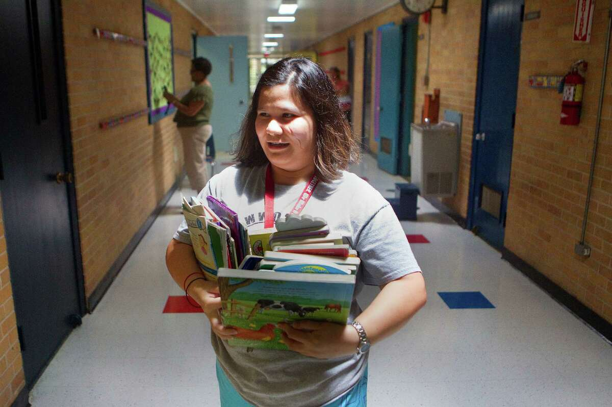 Valerie Arceo delivers books to classrooms this week at Corpus Christi Catholic School in Houston. Enrollment there is up 7 percent over last year.