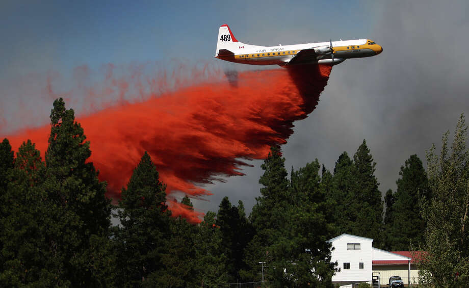 A plane drops retardant to create a fire break at the Sunlight Waters housing development as the Taylor Bridge wildfire advances on the community on Tuesday near Cle Elum. Homes burned in the neighborhood and propane tanks could be heard during the day venting their contents in jets of fire. Photo: JOSHUA TRUJILLO / SEATTLEPI.COM