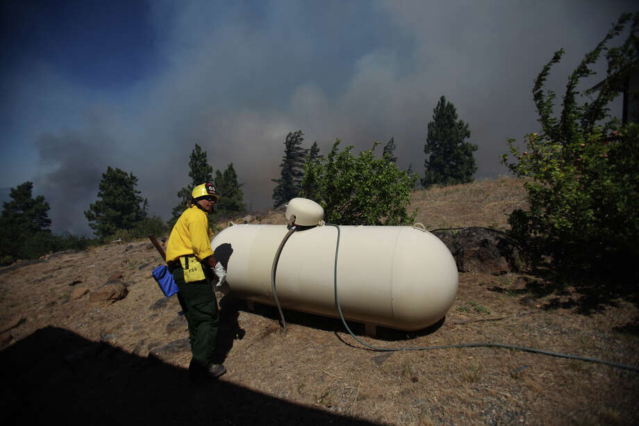 Firefighters remove flammable material from near houses at the Sunlight Waters housing development as the Taylor Bridge wildfire advances on the community on Tuesday, August 14, 2012 near Cle Elum. Photo: JOSHUA TRUJILLO / SEATTLEPI.COM