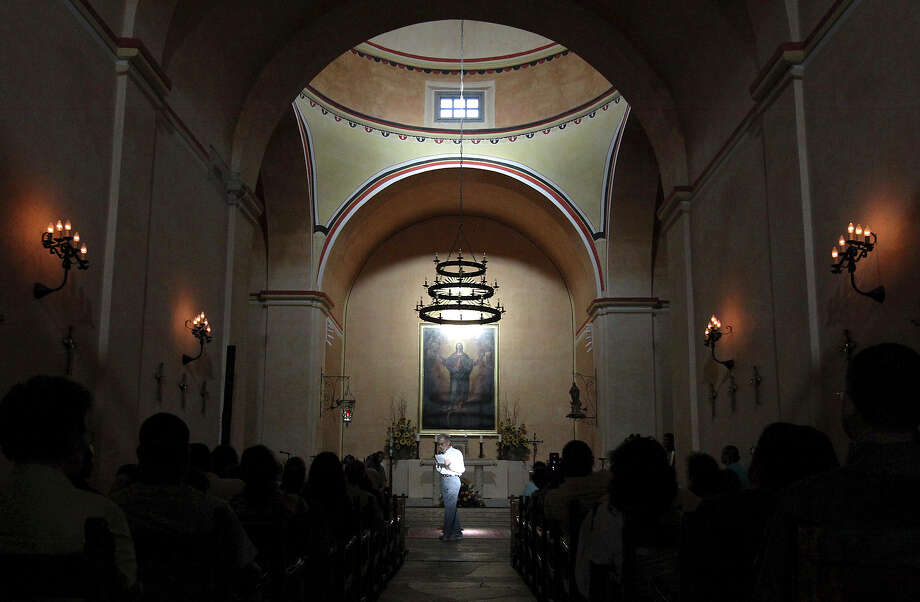 Mission Concepcion docent George Dawson stands in the sunlight that streams through a window to the church's center. Photo: Kin Man Hui, San Antonio Express-News / ©2012 San Antonio Express-News