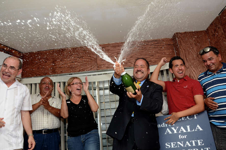 Andres Ayala, Jr. sprays his supporters with champagne as he claims victory during the 23rd District State Senate primary at Ayala's campaign headquarters located at 2484 East Main St. in Bridgeport on Tuesday, Aug. 14, 2012. Supporting Ayala on stage from left campaign manager Americo Santiago, father Andres Ayala, Sr., fiance Carmen Colon, Ayala, son Andres Ayala III, and brother Edwin Ayala. Photo: Amy Mortensen / Connecticut Post Freelance