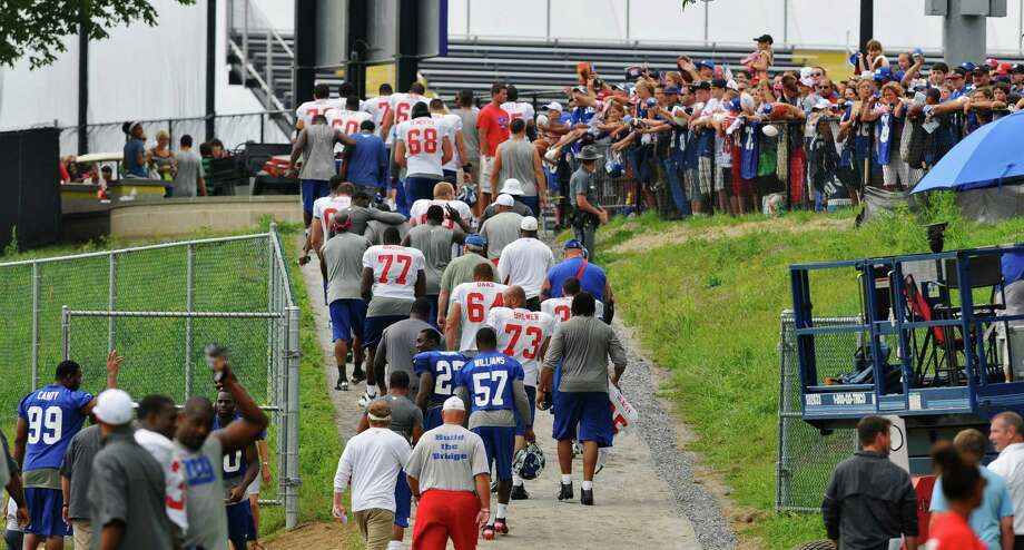 New York Giants players walk off the field as fans wait for autographs at the end of practice on the last day of training camp at UAlbany on Tuesday Aug. 14, 2012 in Albany, NY.  (Philip Kamrass / Times Union) Photo: Philip Kamrass / 00018767C