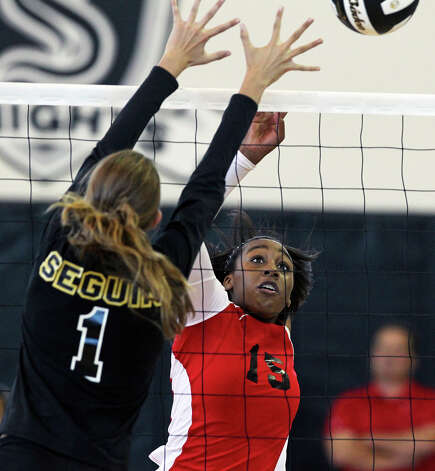 Yanesha Johnson (15) flips the ball past Darian Bugai as New Braunfels Canyon beats Seguin 3-0 at Steele High School gym on Tuesday, Aug. 14, 2012. Photo: Tom Reel, San Antonio Express-News / ©2012 San Antono Express-News