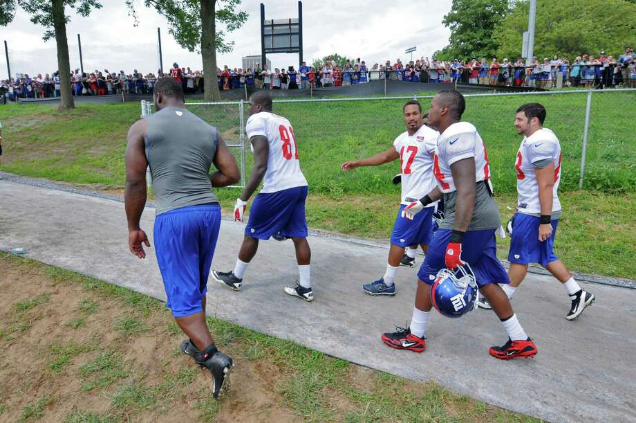 New York Giants players Justin Tuck, Adrien Robinson, Travis Beckum, Christian Hopkins and Joe Martinek, left to right, walk off the field as fans wait for autographs at the end of practice on the last day of training camp at UAlbany on Tuesday Aug. 14, 2012 in Albany, NY.  (Philip Kamrass / Times Union) Photo: Philip Kamrass / 00018767C