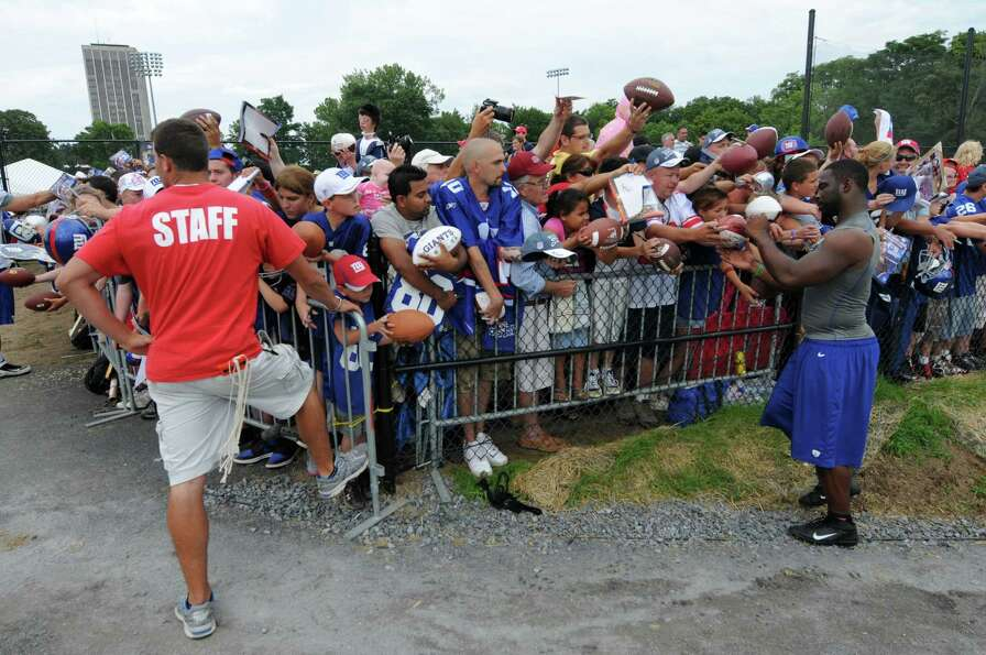 New York Giants defensive end Justin Tuck signs autographs at the end of practice on the last day of
