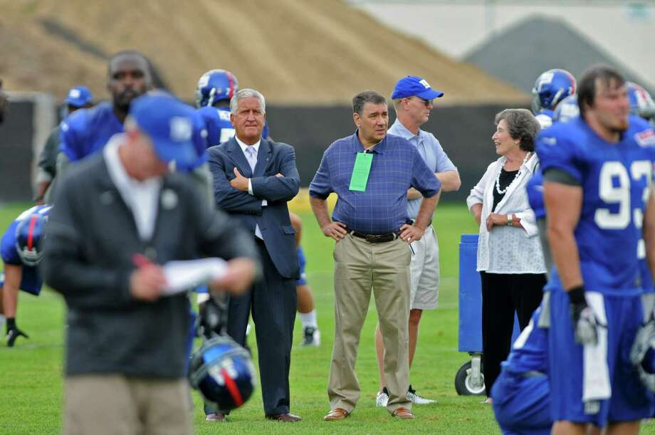 Albany Mayor Jerry Jennings, arms folded,  watches practice with UAlbany President George Philip, center, while New York Giants co owner John Mara talks with former UAlbany President   Karen Hitchcock, right, on the last day of training camp at UAlbany on Tuesday Aug. 14, 2012 in Albany, NY.  New York Giants head coach Tom Coughlin is in left foreground.  (Philip Kamrass / Times Union) Photo: Philip Kamrass / 00018767C