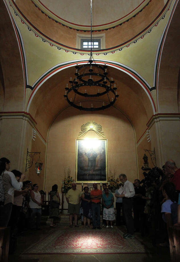 Mission Concepción docent George Dawson talks to guests about the unique path of light which enters the church from a window on Tuesday, August 14, 2012. The solar illumination is a yearly phenomenon and one that is seen as symbolic since the light crosses right in the middle of the cruciform church. Guests and parishioners attended the event and celebrated the solar illumination as well as had Mass for the Feast of the Assumption. Photo: Kin Man Hui, Kin Man Hui / Express-News / ©2012 San Antonio Express-News