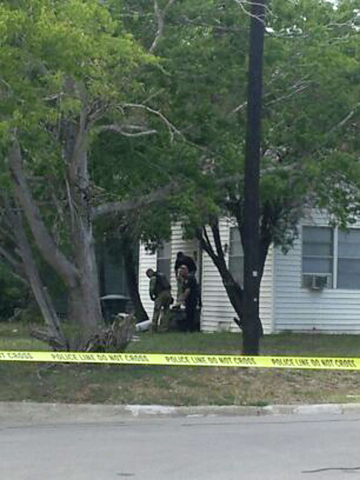 Authorities are seen outside a house near Texas A&M University, where the shootout took place on Monday. A constable, a renter and a bystander were killed.