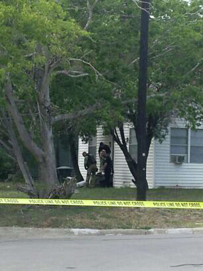 Authorities are seen outside a house near Texas A&M University, where the shootout took place on Monday. A constable, a renter and a bystander were killed. Photo: Associated Press / AP