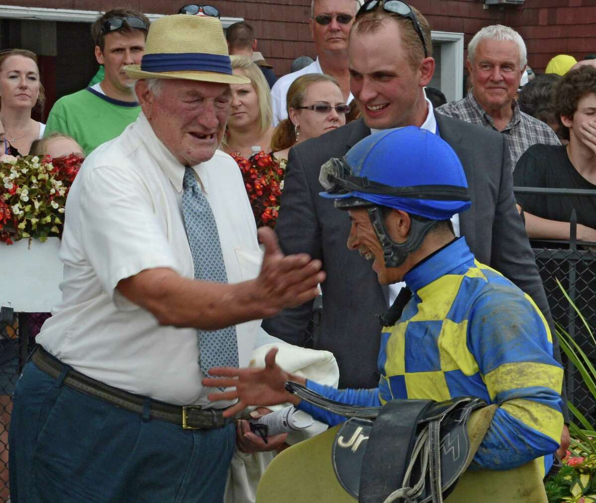 Trainer H. Allen Jerkens gives jockey Junior Alvarado a playful tap on the cheek after he rode Emma's Encore to the win in The Prioress Stakes at the Saratoga Race Course in Saratoga Springs, N.Y. August 4, 2012. (Skip Dickstein/Times Union)