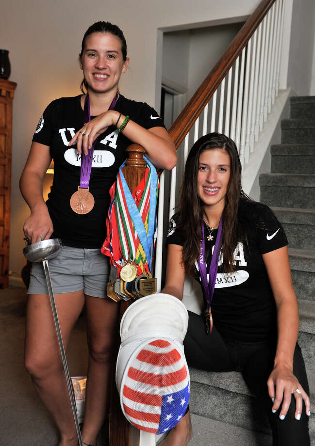Courtney (left) and Kelley Hurley happily display the team bronze medals they won at the Olympics. Both have been surprised by the receptions they received upon returning home. Photo: Robin Jerstad, For The Express-News