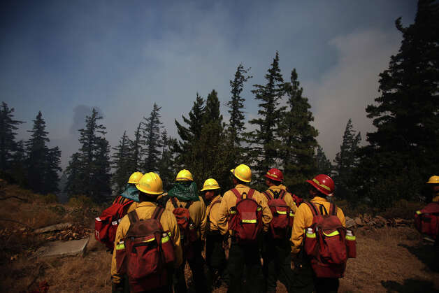 Firefighters gather to plan their strategy near the Sunlight Waters housing development as the Taylor Bridge wildfire advances. Photo: JOSHUA TRUJILLO / SEATTLEPI.COM