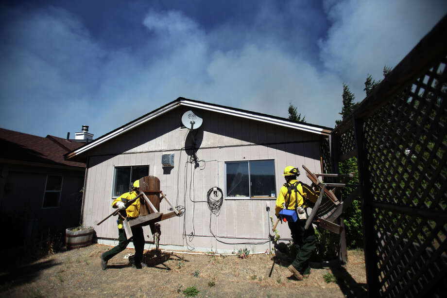 Firefighters remove flammable material from near a home in the Sunlight Waters housing development as the Taylor Bridge wildfire advances on the community, Photo: JOSHUA TRUJILLO / SEATTLEPI.COM