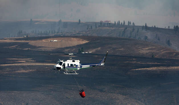 A helicopter works the scene as the Taylor Bridge wildfire burns near Cle Elum. Photo: JOSHUA TRUJILLO / SEATTLEPI.COM
