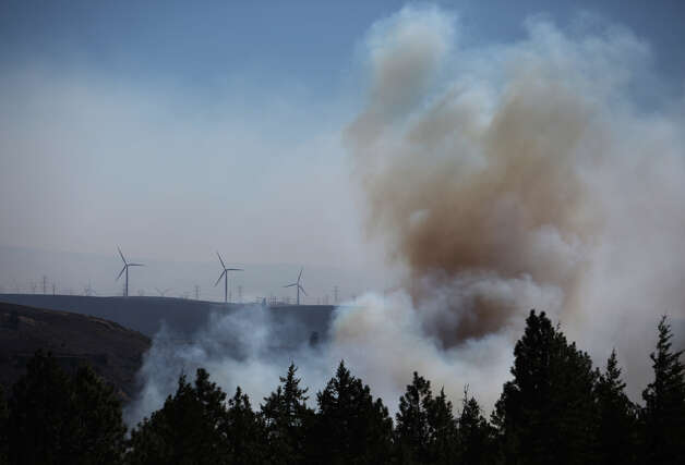 Windmills turn in a stiff breeze as the Taylor Bridge wildfire advances. Photo: JOSHUA TRUJILLO / SEATTLEPI.COM
