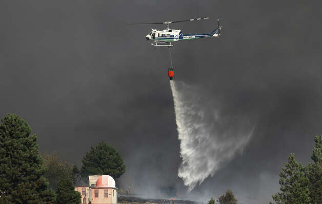 A helicopter drops water at the Sunlight Waters housing development. Photo: JOSHUA TRUJILLO / SEATTLEPI.COM