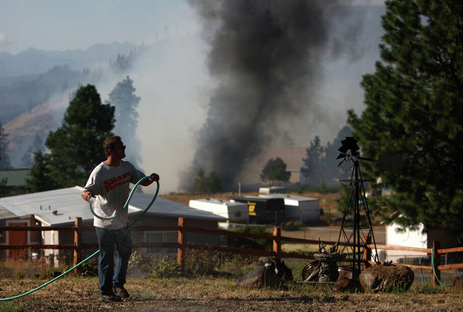 Kris Hjaltalin wets the ground outside his home in the Sunlight Waters housing development as the Taylor Bridge wildfire advances on the community. Photo: JOSHUA TRUJILLO / SEATTLEPI.COM