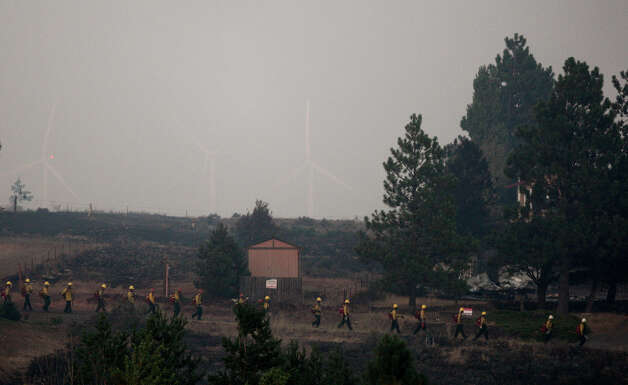 Firefighters march through a burned area of the Sunlight Waters housing development. Photo: JOSHUA TRUJILLO / SEATTLEPI.COM