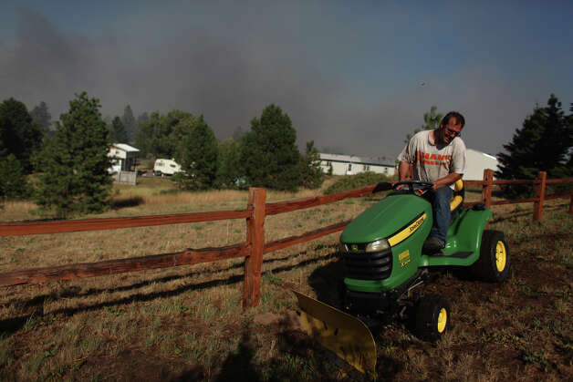 Kris Hjaltalin uses a lawn tractor to create a fire break outside his home in the Sunlight Waters housing development as the Taylor Bridge wildfire advances on the community. Photo: JOSHUA TRUJILLO / SEATTLEPI.COM