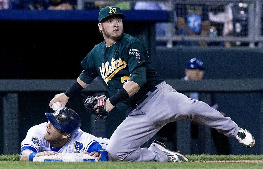 After failing to tag Kansas City Royals' Alex Gordon (4), Oakland Athletics third baseman Josh Donaldson (20) looks for a play on an RBI single by Alcides Escobar in the fifth inning during Tuesday's baseball game on August 14, 2012, at Kauffman Stadium in Kansas City, Missouri. (John Sleezer/Kansas City Star/MCT) Photo: John Sleezer, McClatchy-Tribune News Service