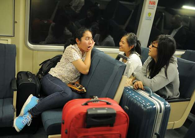 Putri Siti Dyannie, left, talks to her friends on BART on their way to the airport for their summer vacation to New York on Friday, July 27, 2012 in San Francisco, Calif. Photo: Yue Wu, The Chronicle