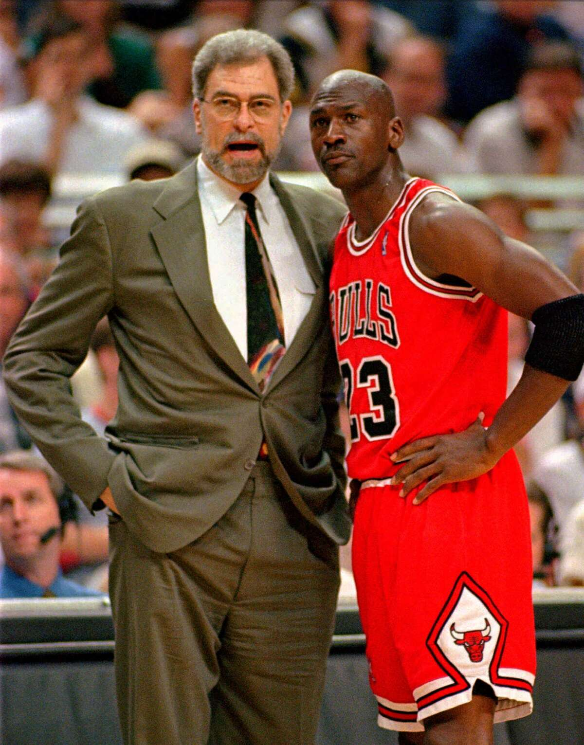 Chicago Bulls head coach Phil Jackson, left, and guard Michael Jordan talk during a timeout in their Eastern Conference Final game in 1996 in Orlando. Jackson was up in the stands at Glens Falls Civic Center one day in 1984 when he witnessed a younger Jordan display his prowess on the Chicago Bulls team in a winning game against the New York Knicks.
