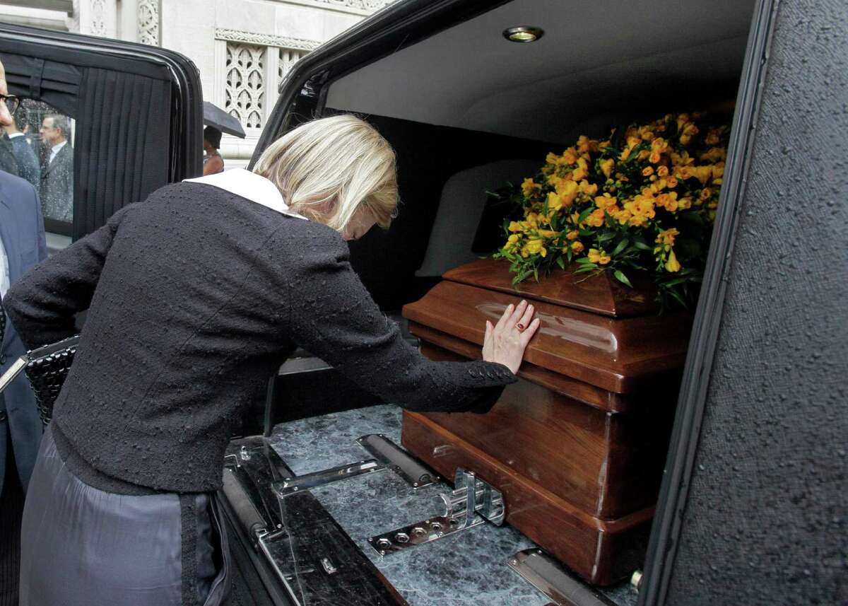 """Terre Blair, wife of Marvin Hamlisch, places her hand on his casket in a hearse after his funeral service, in New York's Temple Emanu-El, Tuesday, Aug. 14, 2012. Hamlisch composed or arranged hundreds of scores for musicals and movies, including """"A Chorus Line"""" on Broadway and the films """"The Sting,"""" ''Sophie's Choice,"""" ''Ordinary People"""" and """"The Way We Were."""" He won three Oscars, four Emmys, four Grammys, a Tony, a Pulitzer and three Golden Globes. Hamlisch died Aug. 6 in Los Angeles at age 68."""