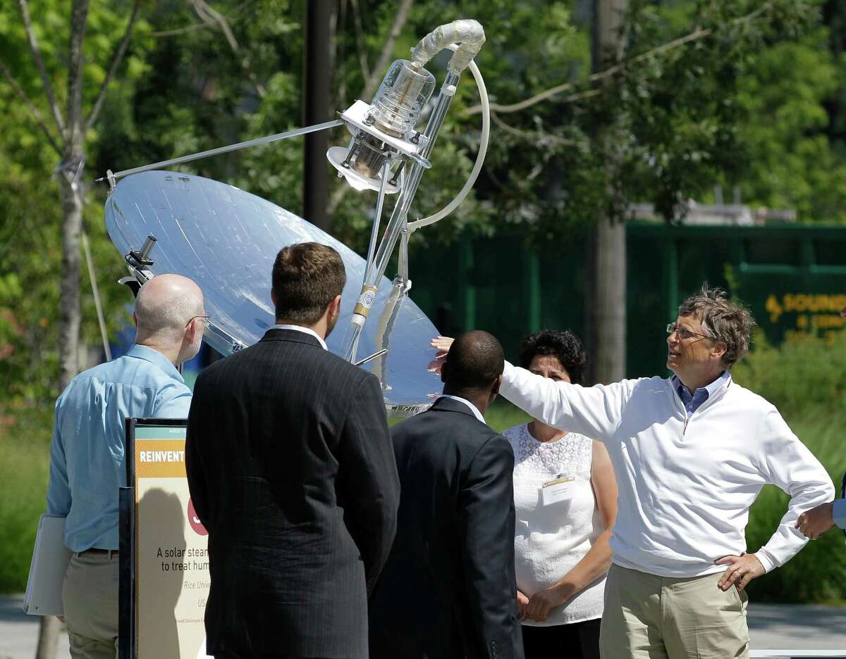 Bill Gates, right, looks at a device that uses solar energy to treat human waste, as he tours the
