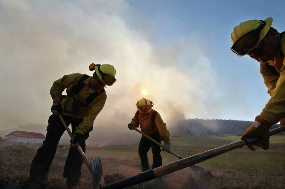Firefighters work to create a break from the fire burning behind them Tuesday,, on Bettas Road near Cle Elumh.  (AP Photo/Elaine Thompson) Photo: Associated Press