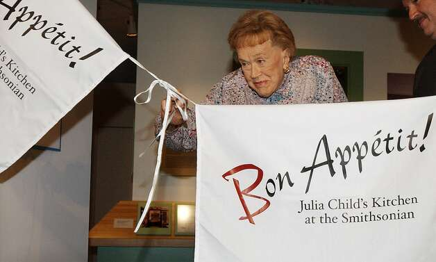 Julia Child pulls on apron strings to open her kitchen exhibition at the Smithsonian's National Museum of American History in 2002.  (SFC Archives)