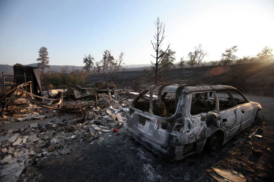 As the sun rises, the smoldering remains of a home are shown on Wednesday, August 15, 2012 along Highway 10 near Ellensburg. The Taylor Bridge Fire pushed through neighborhoods and rural areas, destroying an estimated 70 homes. Photo: JOSHUA TRUJILLO / SEATTLEPI.COM
