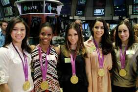 From left, Kyla Ross, Gabby Douglas, McKayla Maroney, Aly Raisman, and Jordyn Wieber, members of the United States women's Olympic gymnastics gold medal-winning team, pose for photos on the floor of the New York Stock Exchange, Tuesday, Aug. 14, 2012, in New York.