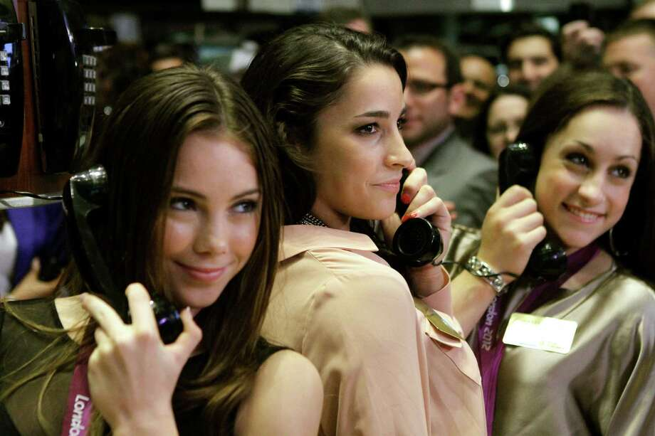 From left, McKayla Maroney, Aly Raisman and Jordyn Wieber, members of the United States women's Olympic gymnastics gold medal-winning team, pretend to talk on telephones while posing for photos on the floor of the New York Stock Exchange, Tuesday, Aug. 14, 2012, in New York. Photo: Alex Katz, AP / AP
