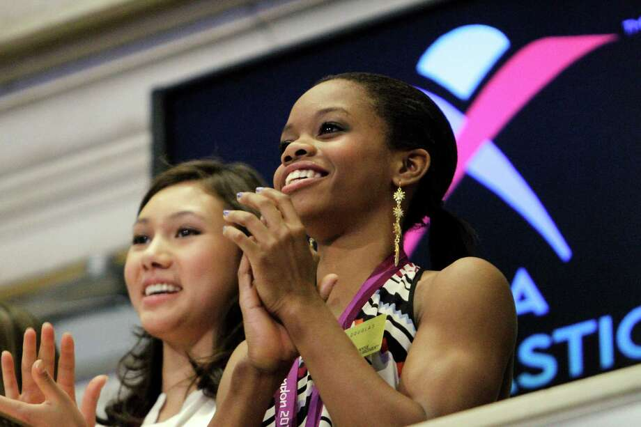 Kyla Ross, left, and Gabby Douglas, members of the United States women's Olympic gymnastics gold medal-winning team, clap their hands on the balcony of the New York Stock Exchange where they and three others rang the closing bell, Tuesday, Aug. 14, 2012, in New York. Photo: Alex Katz, AP / AP