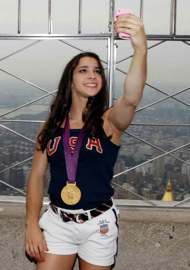 Aly Raisman, of the 2012 US Women's Gymnastics Olympic Team, takes a photo of herself on the observation deck of the Empire State Building, Tuesday, Aug. 14, 2012 in New York. Photo: Jason DeCrow, JASON DECROW/INVISION/AP / Invision