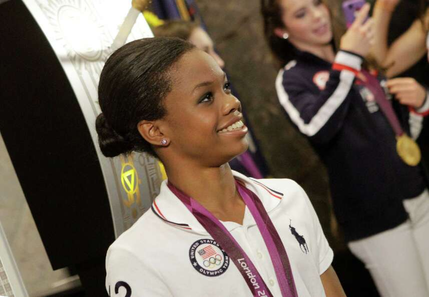 U.S. Women's Gymnastics Olympic team gold-medal winner Gabby Douglas poses with team members at the