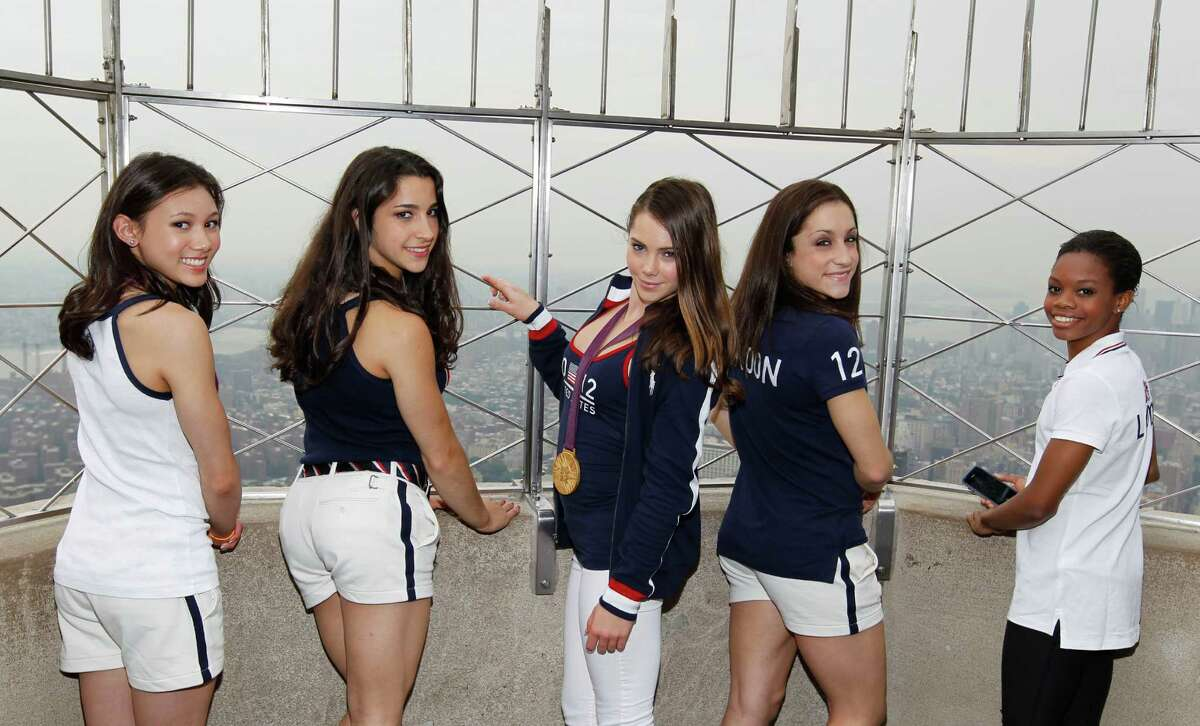 Members of the 2012 US Women's Gymnastics Olympic Team, from left, Kyla Ross, Aly Raisman, McKayla Maroney, Jordyn Wieber and Gabby Douglas pose on the observation deck of the Empire State Building, Tuesday, Aug. 14, 2012 in New York.