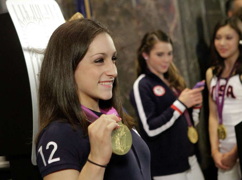 U.S. Women's Gymnastics Olympic team gold-medal winner Jordyn Wieber, left, poses with her medal at the Empire State Building, Tuesday, Aug. 14, 2012 in New York. Photo: Alex Katz, AP / AP