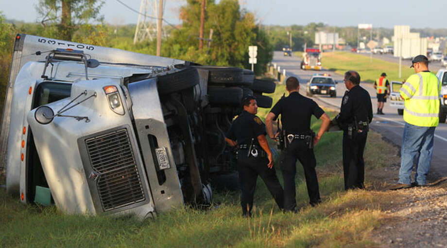 San Antonio police investigate the scene at Fischer road and Interstate 35 northbound where a big rig hauling shrink wrap listed over on its side Wednesday August 15, 2012 at about 6:30 a.m. after a woman driving the rig took a brief nap. After waking up, the driver attempted to get back on the road and the truck tipped over on its side. The woman suffered a minor injury to her head and traffic in the area was not affected. John Davenport/2012 San Antonio Express-News