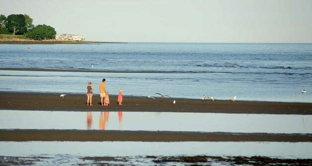 A family spends a summer evening at on Long Island Sound in Southport, Conn. on Saturday July 21, 2012. Photo: Cathy Zuraw / Connecticut Post