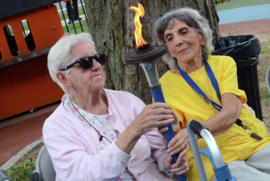 Helen Trombetta, at right, passes the World Harmony torch to Marge Meury during the World Harmony Run stop at The Marvin in Norwalk on Tuesday, Aug. 14, 2012. The World Harmony run is a global torch relay in which torches were lit to travel to over 100 countries to promote international friendship and understanding. Photo: Amy Mortensen / Connecticut Post Freelance