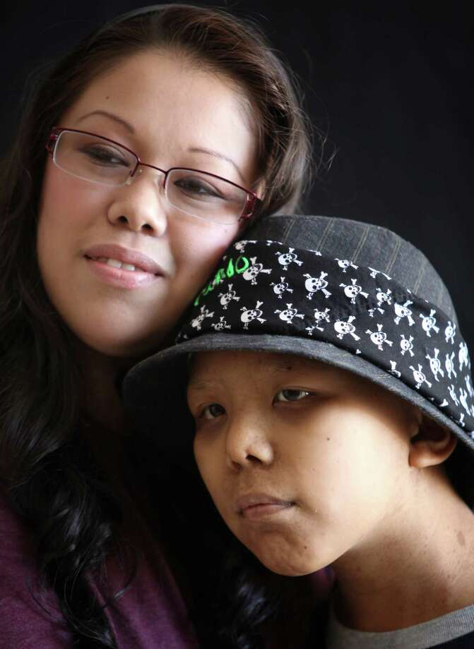 Claudia Javier and her son Orlando Javier-Ruiz, 11, pose during a portrait session Tuesday July 31, 2012 at the Children's Cancer Center in Christus Santa Rosa Hospital. Patients and families were beautified and photographed as part of Flashes of Hope, a national non-profit organization that joined volunteer Aveda Institute estheticians and volunteer photographers. Photo: Julysa Sosa / SAN ANTONIO EXPRESS-NEWS